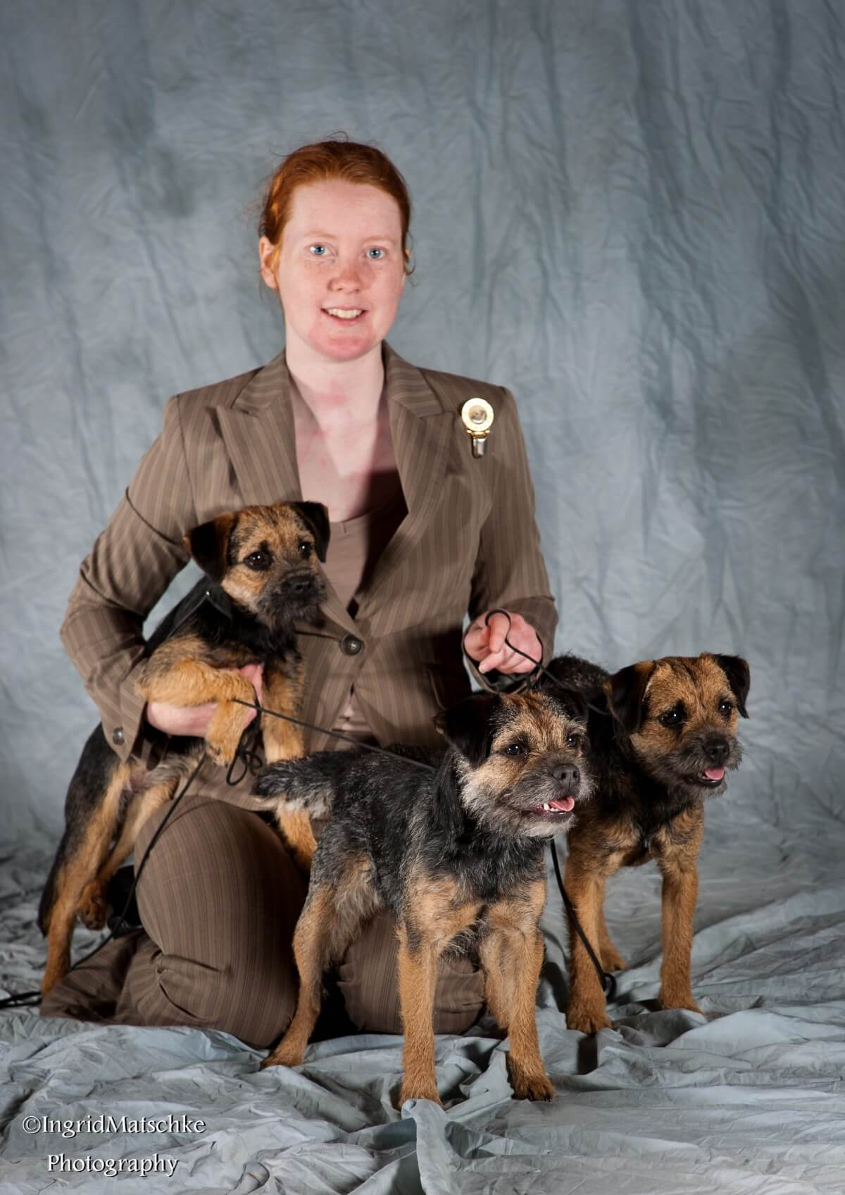 Tegan Whalan posing with a selection of her Border Terriers.